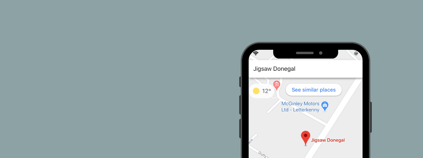 Grey background with an iphone that's searching Jigsaw Donegal on maps