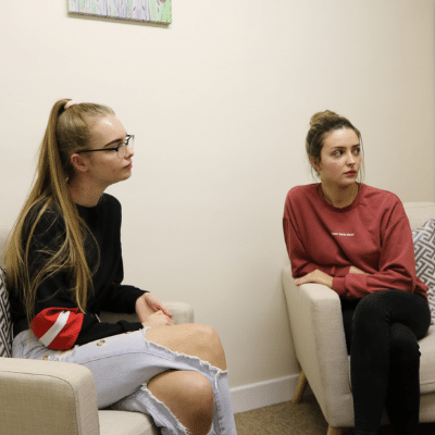 Two people sitting on chairs in a waiting area