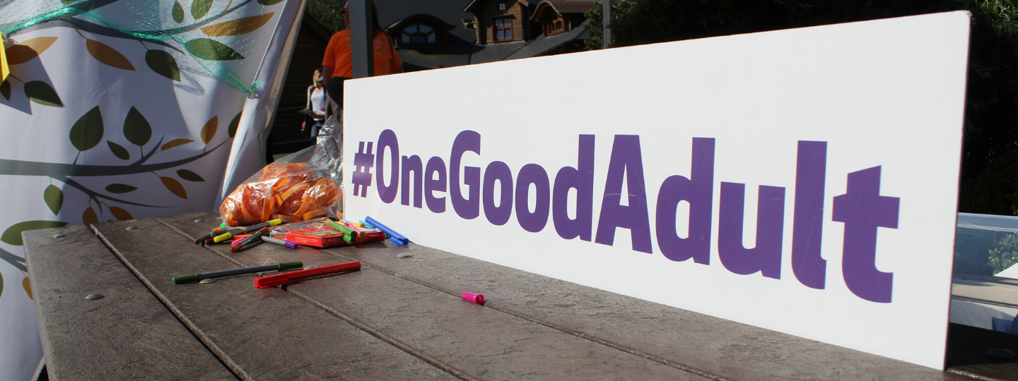 a white sign with purple letters that says hashtag one good adult