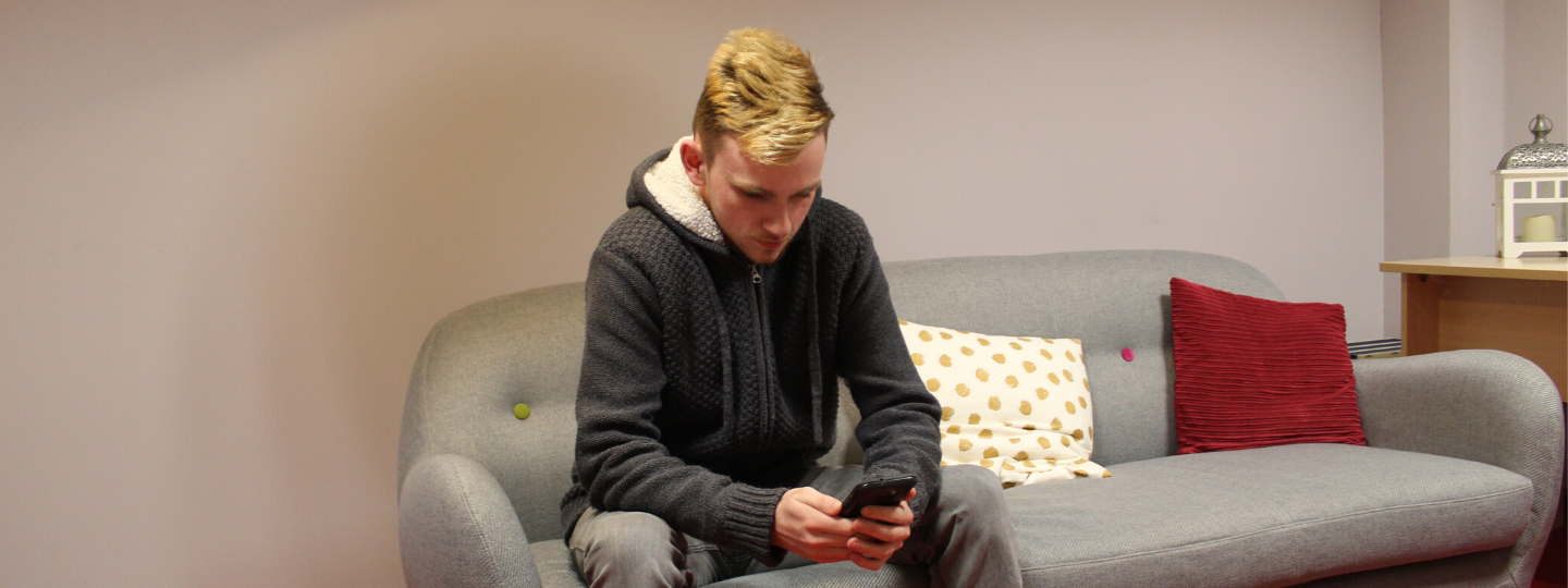 young man on a sofa on his phone