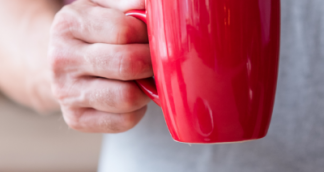 Person holding a bright red cup