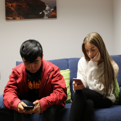 Two young people sitting on a couch on their phones