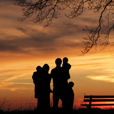 Shadows of a family of five looking out into a sunset