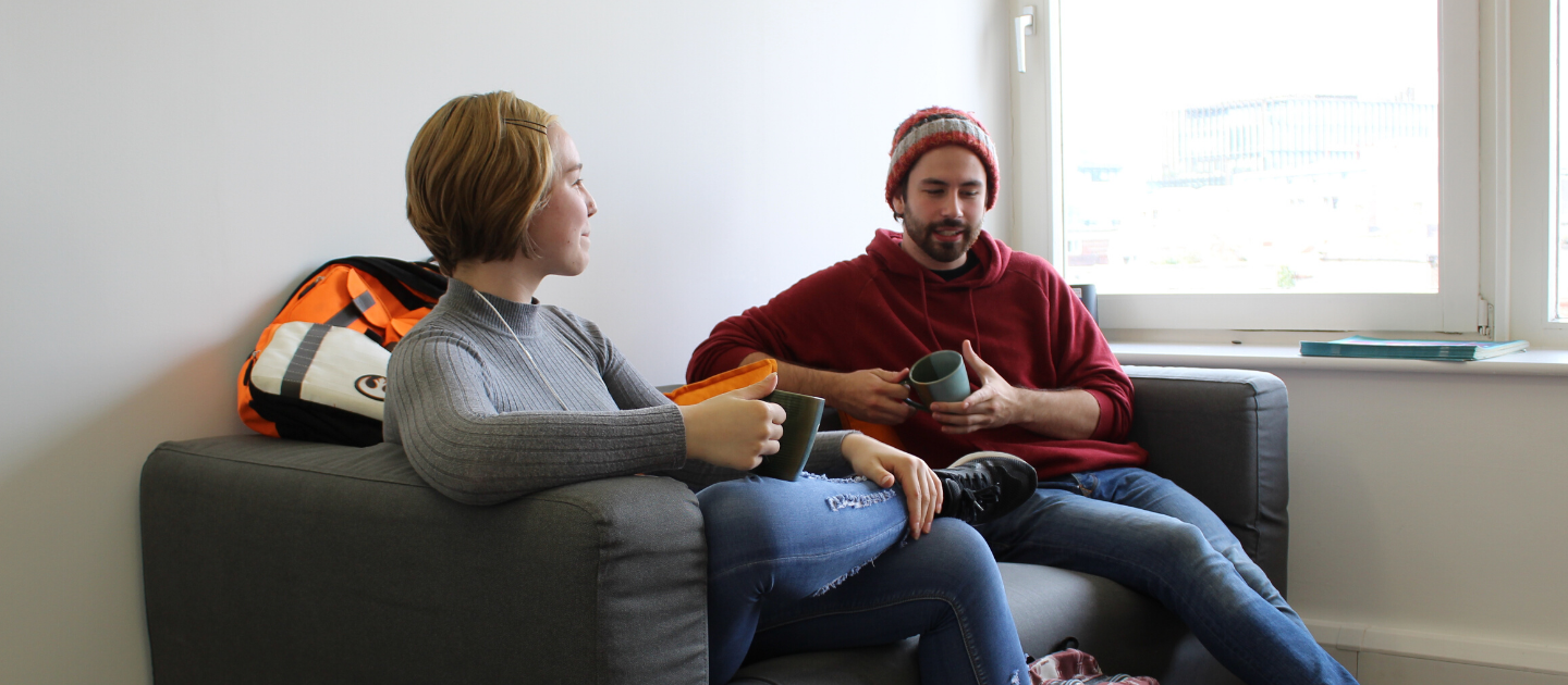 Young woman and young man sitting on a couch, mugs in hand, talking