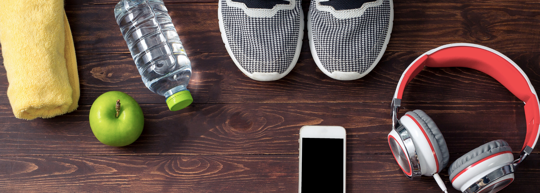 a collection of workout accessories, bottle of water, apple, ipod, headphones, running shoes