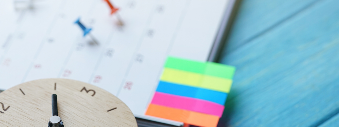 picture of a calendar with pins designating certain dates, post its notes, and a clock signifying a routine