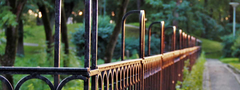 black wire fence alongside a trail