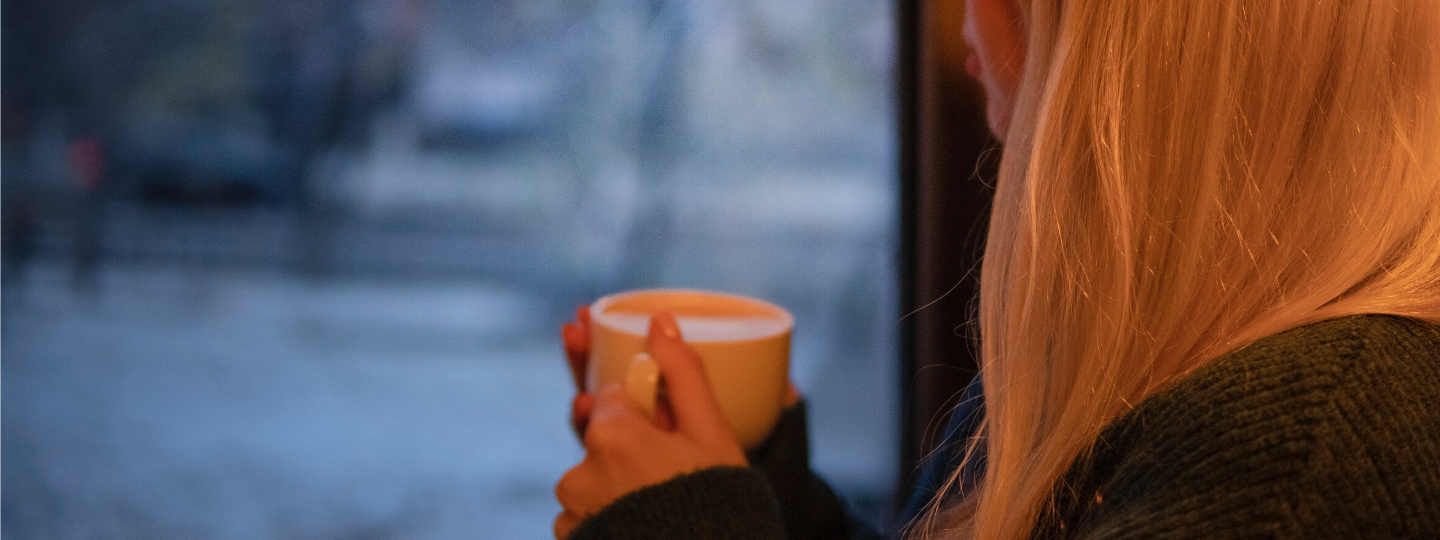 Close up of a woman holding a mug looking outside a window