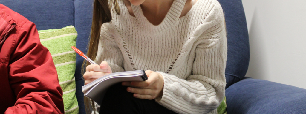 Close up of a young girl writing in a notebook