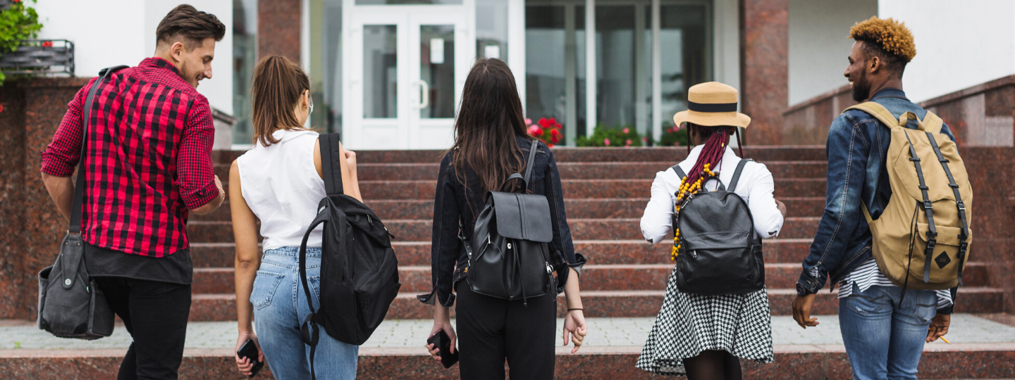 a group of young people walking up a flight of stairs with backpacks, backs turned