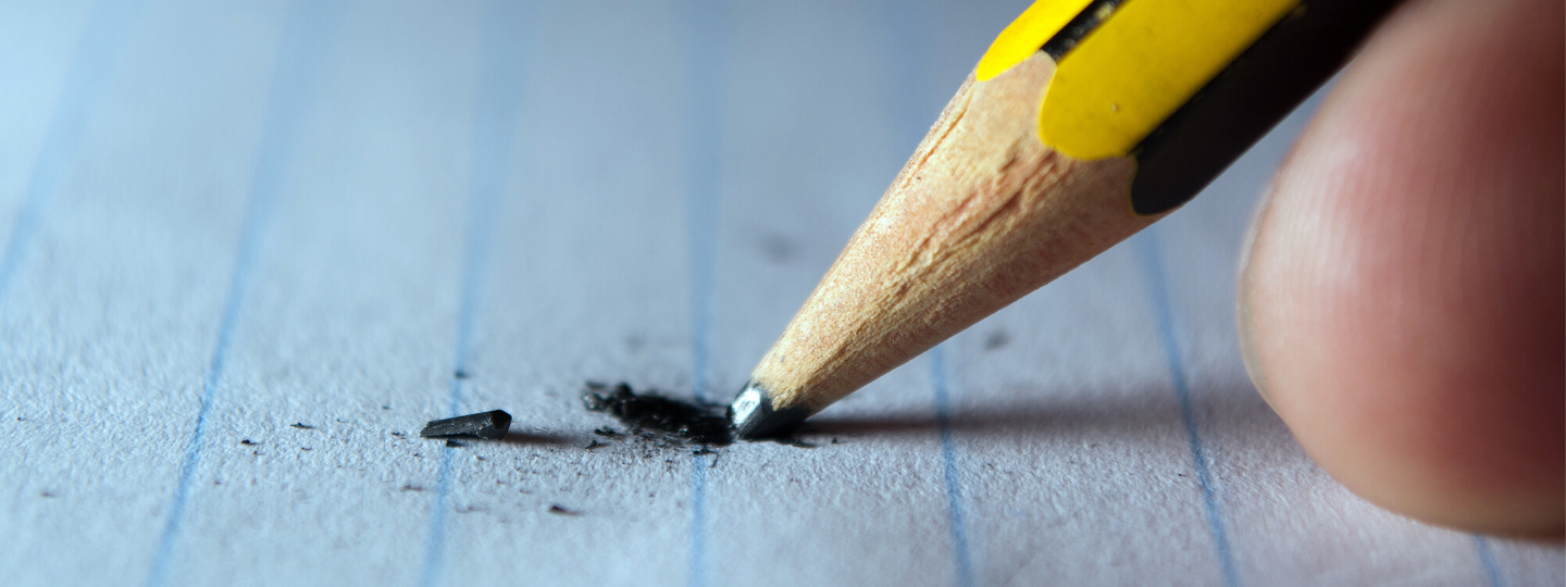 Close up of a pencil being pushed on paper and breaking