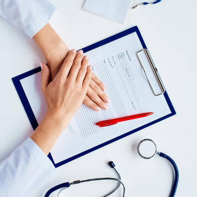 Doctor with hands place on patient form with stethoscope also on table