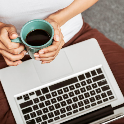 a persona holding a cup of coffee at a laptop