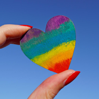 person holding a small rainbow heart