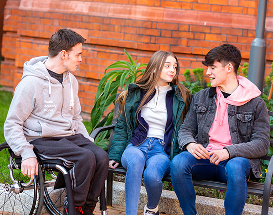 Picture of young people chatting,with one in a wheelchair