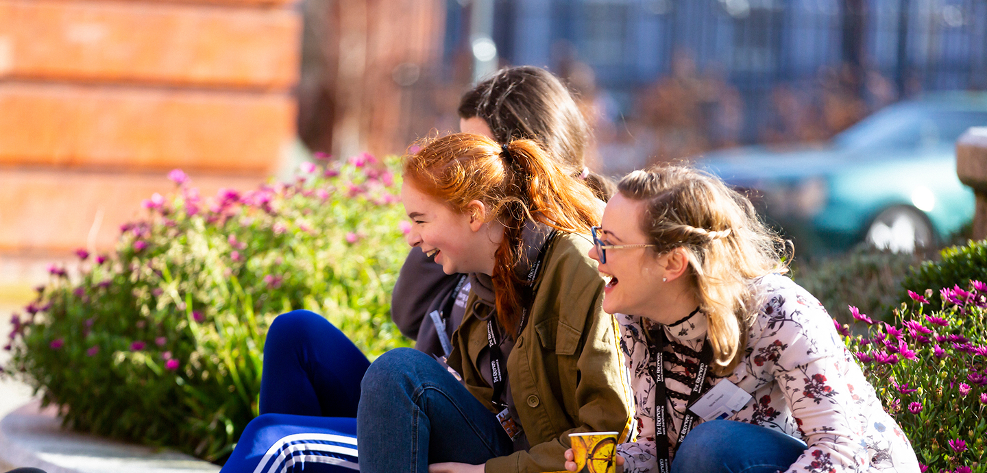young people laughing sitting on the ground