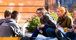Picture of a young woman laughing with others outside