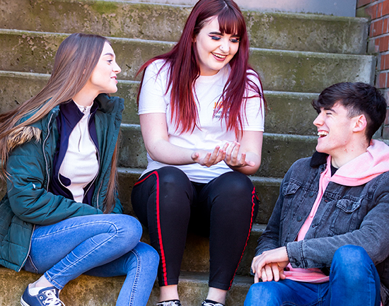 three young people sitting and laughing on steps