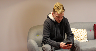 Picture of a young man sitting down looking at his phone