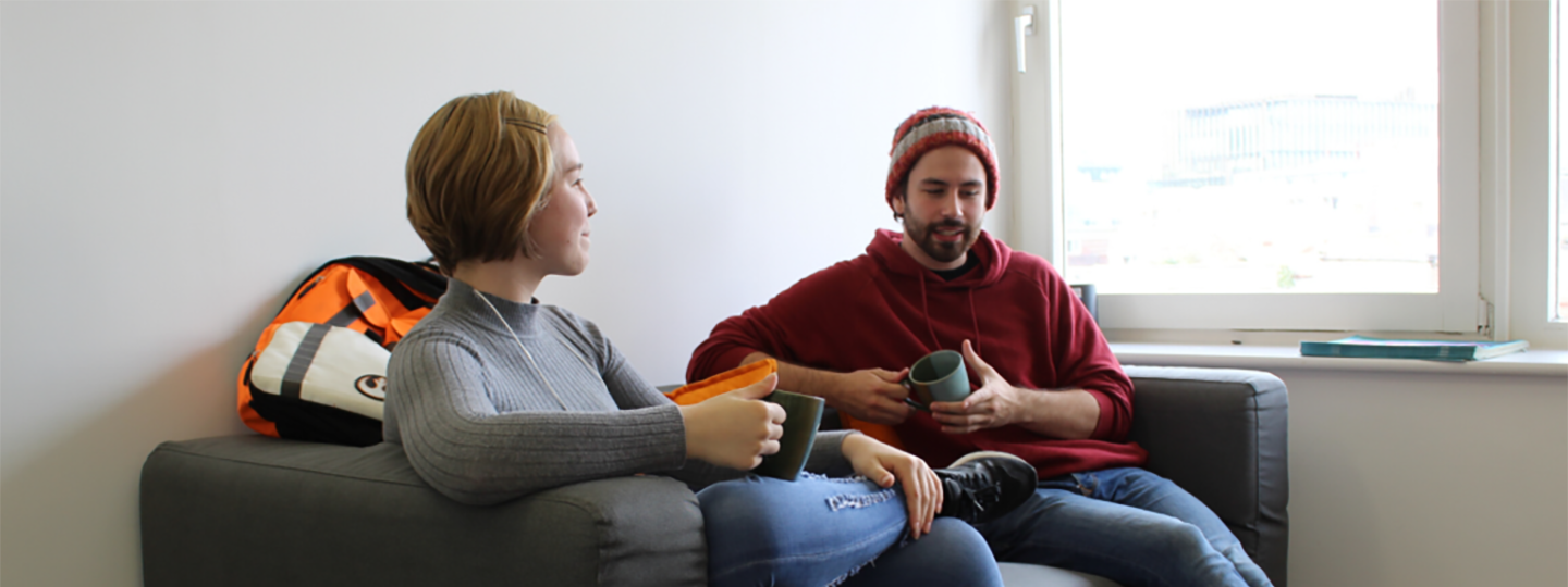 young man and woman sitting on sofa drinking coffee