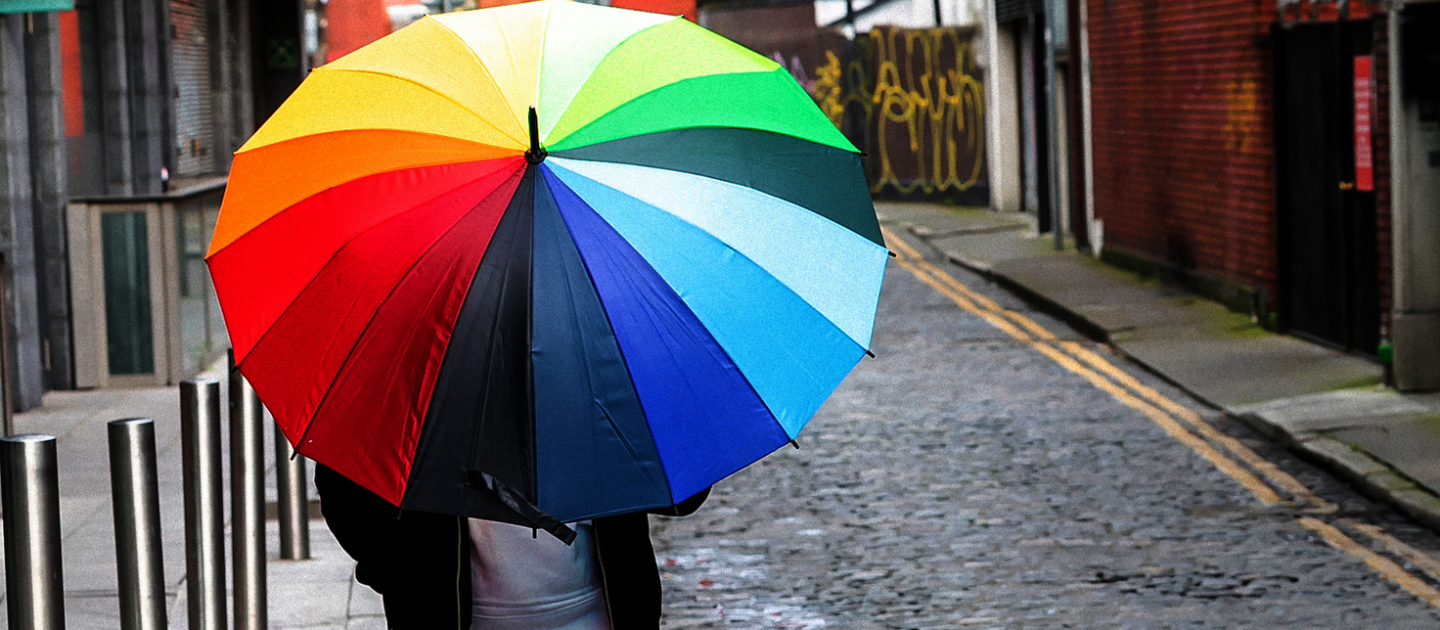 man walking along with coloured umbrella