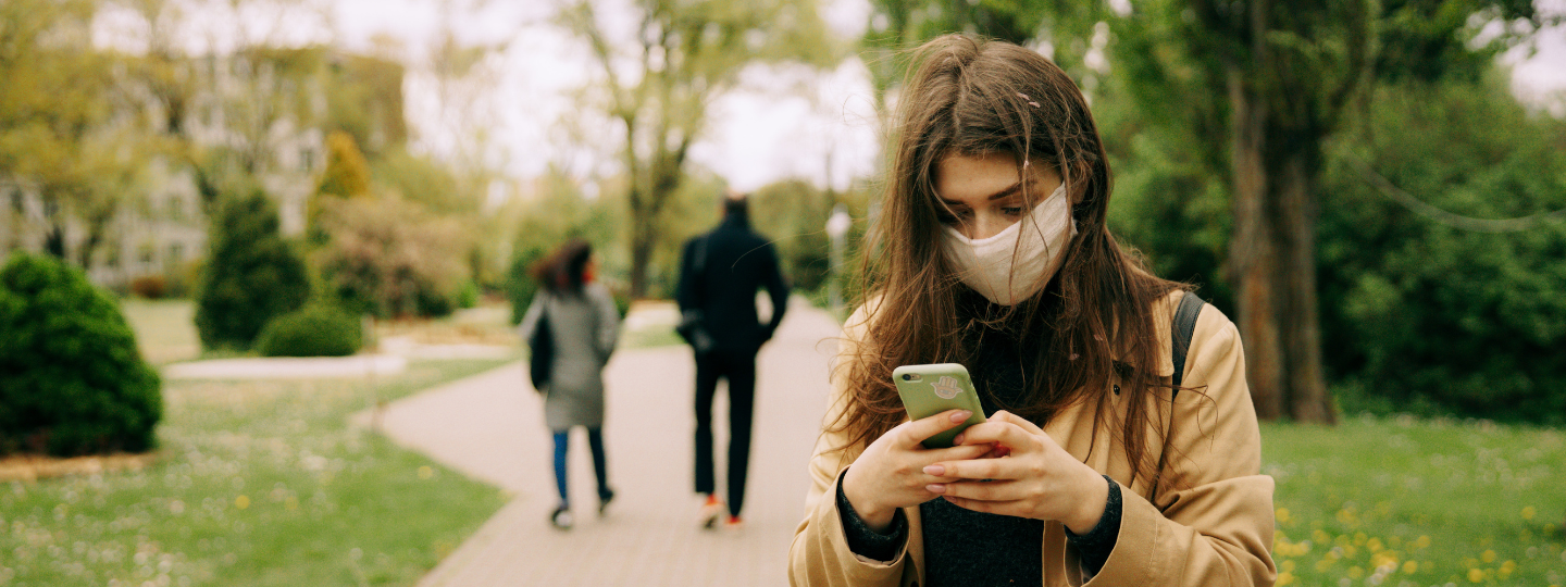 image of girl on her phone wearing a face mask