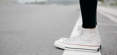 picture of a person wearing converse runners standing on a white painted line
