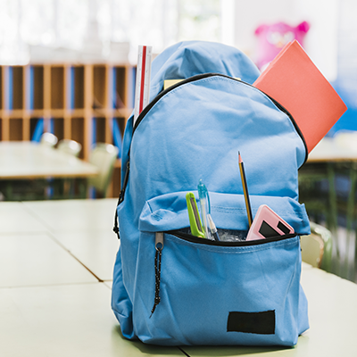 school rucksack with pencil case items hanging out