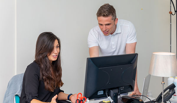 Clinician and clinical manager talking looking at computer
