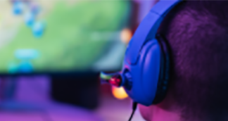 gamer with headphones on from behind looking at screen
