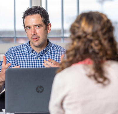 Man talking to woman from behind laptop
