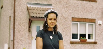 Amina, one of our volunteers in front of her house with cycling helmett