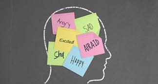 head drawn on a chalkboard with postits saying afraid and happy